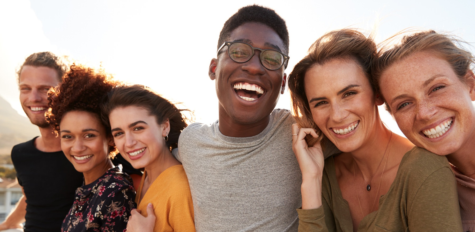 young adults smiling together outdoors while looking at the camera