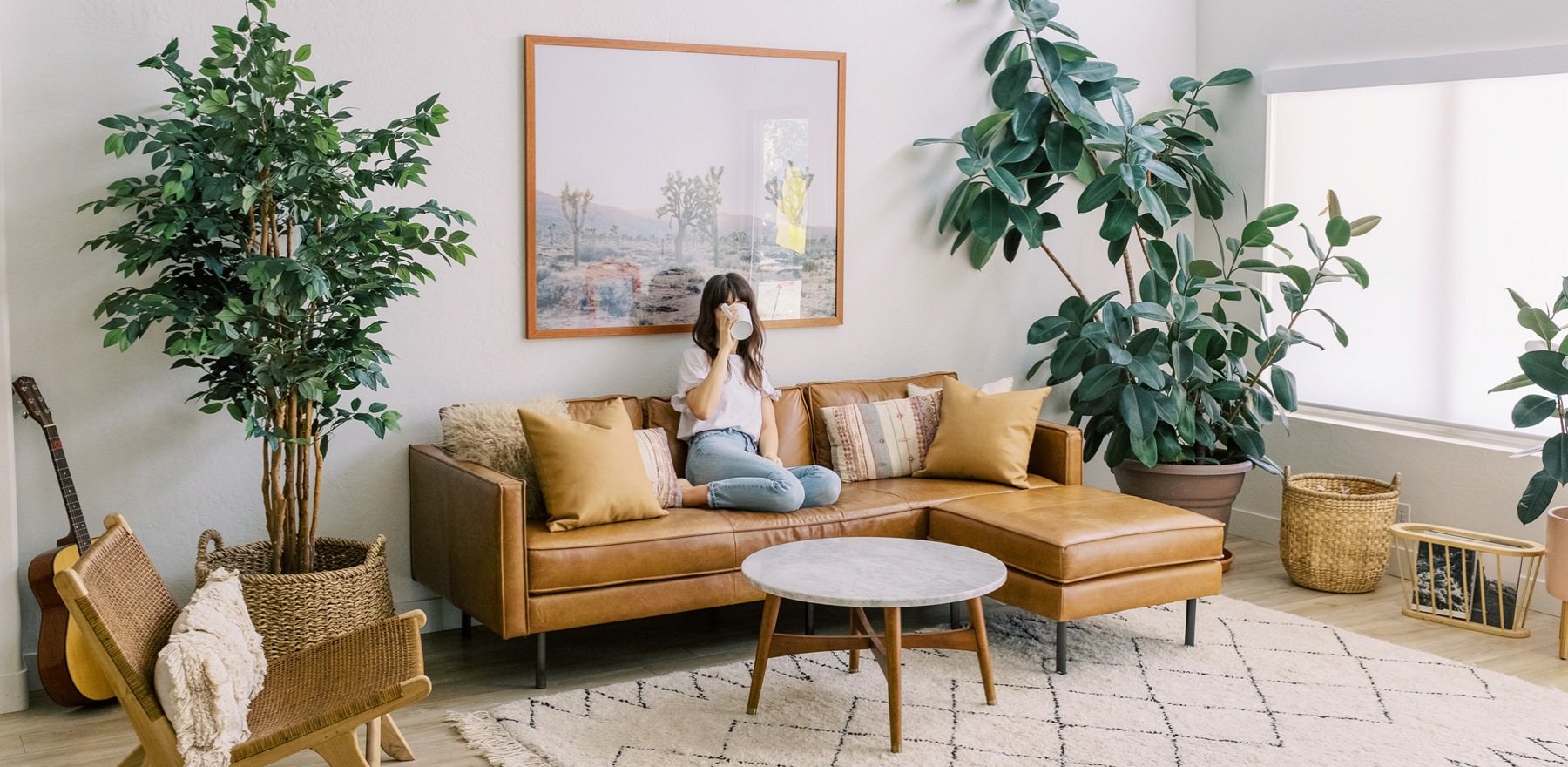 young woman sits on her couch while holding her coffee cup in front of her face