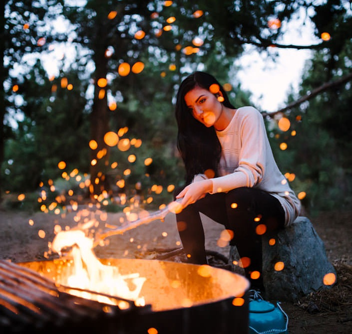 young lady stokes fire in outdoor firepit