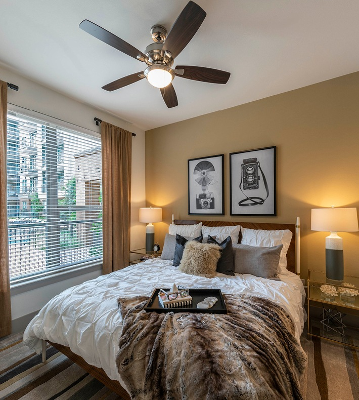 bedroom with ceiling fan, light fixture and large, bright window