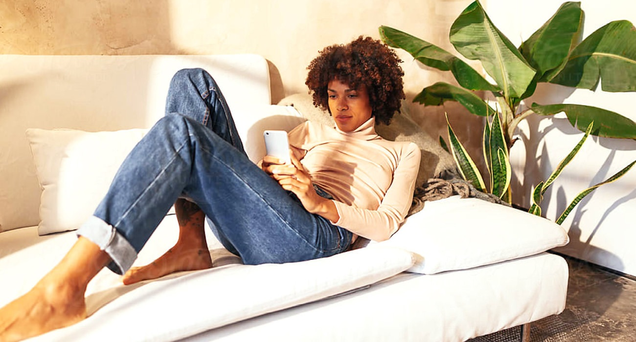 young woman relaxing on couch as she looks at her phone